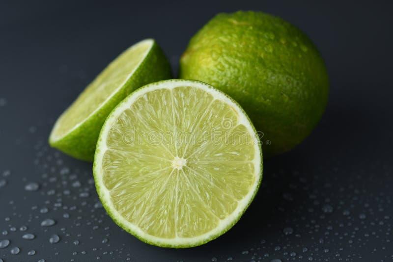 Nya mogna limefrukter p? m?rk bakgrund med vattendroppe arkivbild