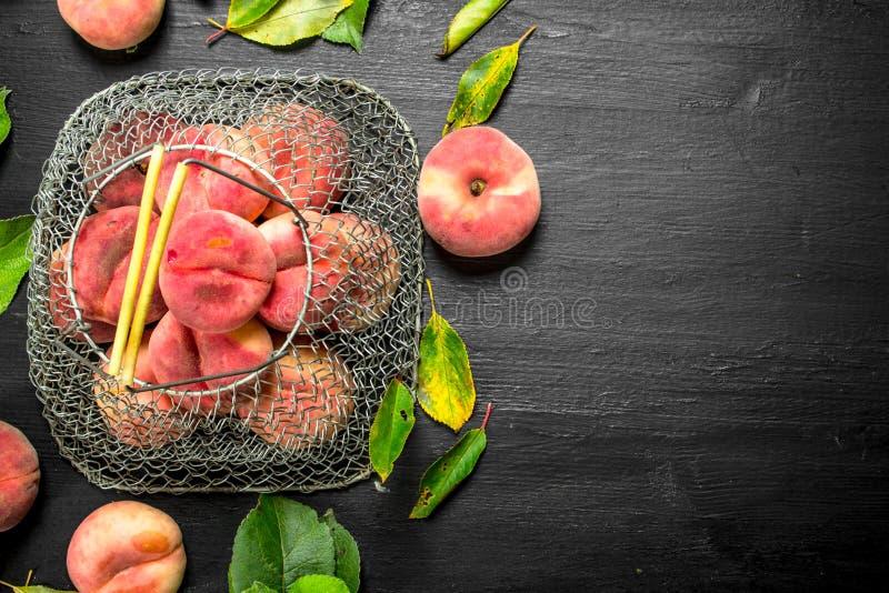 Nya mogna persikor i påse av sidor royaltyfri foto
