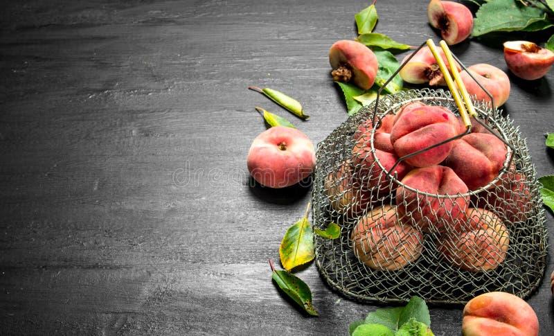 Nya mogna persikor i påse av sidor arkivfoton