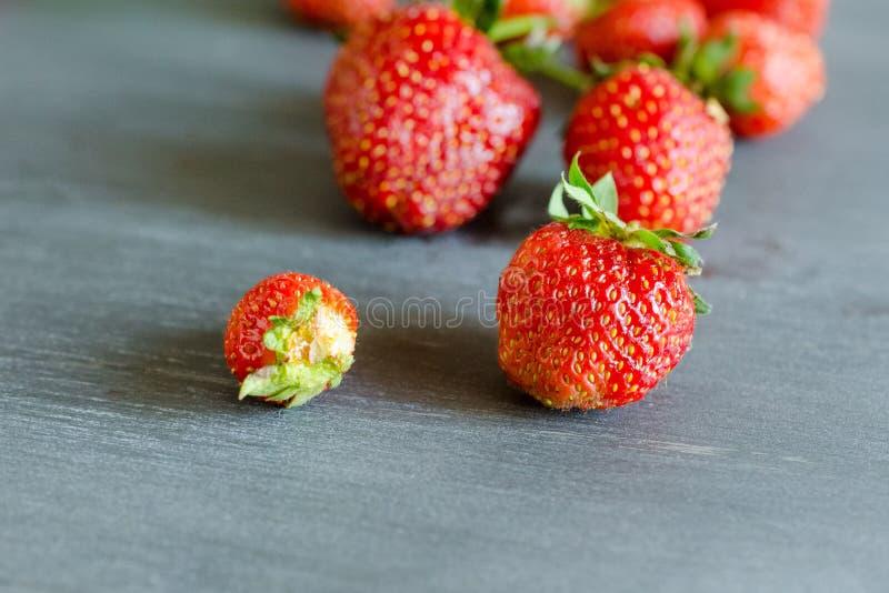 Nya mogna röda jordgubbar på den gråa tabellen Banta sunt, strikt vegetarian royaltyfria bilder