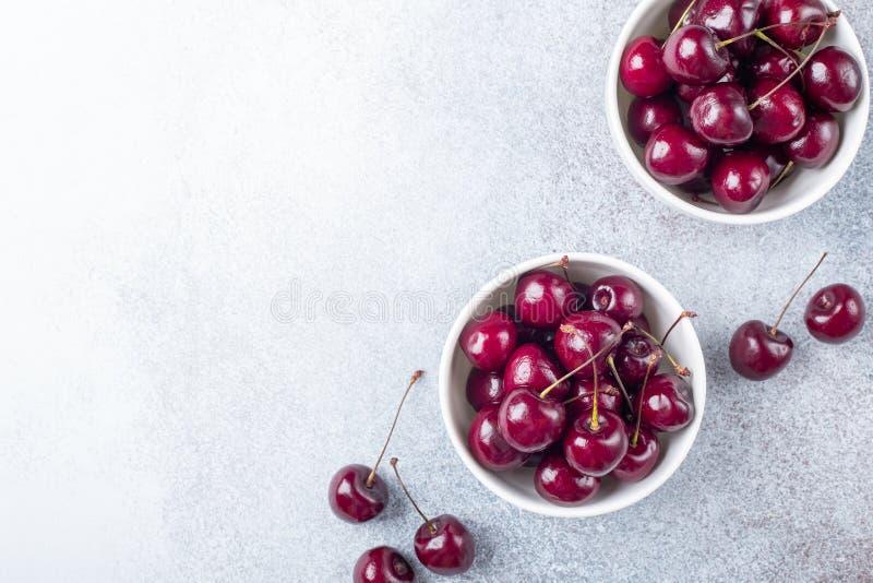 Nya mogna röda körsbär i en vit bunke på ett utrymme för kopia för grå färgstenbakgrund royaltyfria bilder