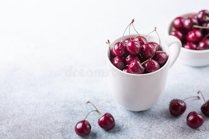 Nya mogna röda körsbär i en vit rånar på en grå färg stenar droppar för bakgrundsCloseupvatten royaltyfria bilder