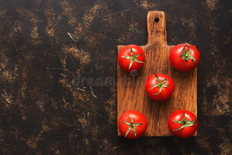 Nya mogna tomater på en skärbräda, mörk bakgrund, bästa sikt En kopia av utrymmet, lekmanna- lägenhet royaltyfri foto