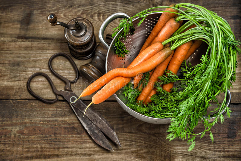 Nya morötter med tappningköksgeråd Mat för landsstil arkivbilder
