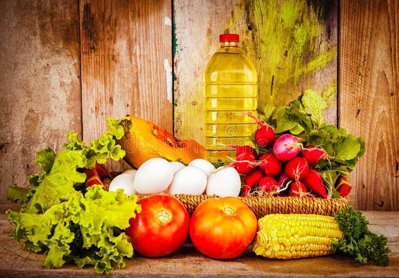 Nya grönsaker, ägg och en buteljera av olja på en korg royaltyfria bilder