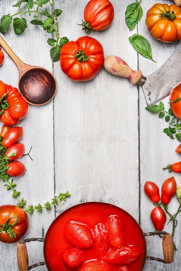 Nya och några hela skalade tomater i matlagningpanna, basilika, träsked och avbrytare på vit lantlig träbakgrund arkivfoton
