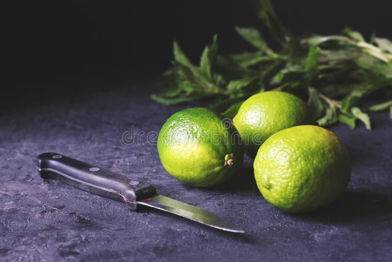 Nya och saftiga gröna och gula limefrukter med mintkaramellen i bakgrunden arkivbild