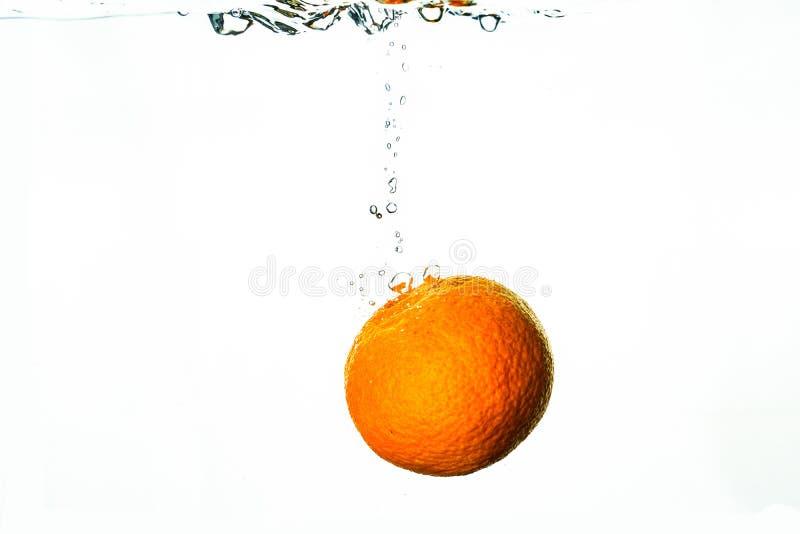 Nya orange nedgångar in i vatten med färgstänk och bubblor fotografering för bildbyråer