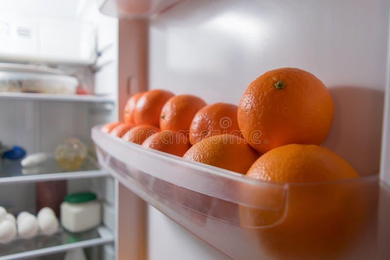Nya orange tangerin ligger på hyllan av kylskåpet arkivbild