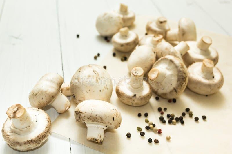 Nya organiska champinjoner och peppar?rtor p? en vit tr?bakgrund arkivbilder
