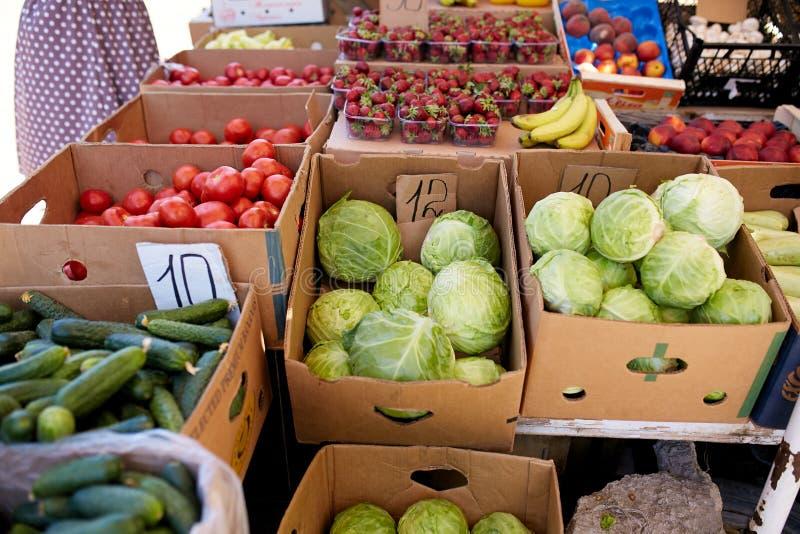 Nya organiska grönsaker och frukter på försäljning på den lokala bondesommaren marknadsför utomhus holdingen för nya händer för m royaltyfri fotografi