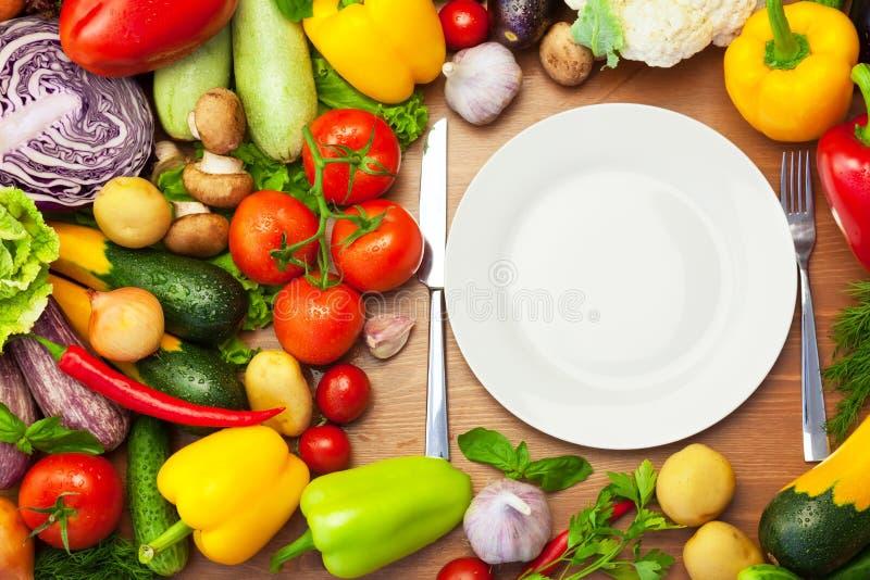 Nya organiska grönsaker runt om den vita plattan med kniven och gaffeln royaltyfri bild