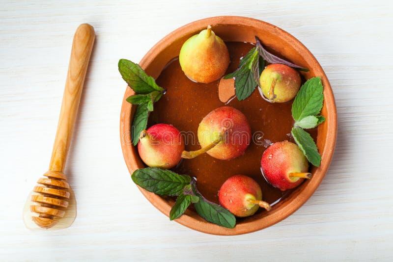 Nya organiska päron med honung i en keramisk platta royaltyfri bild