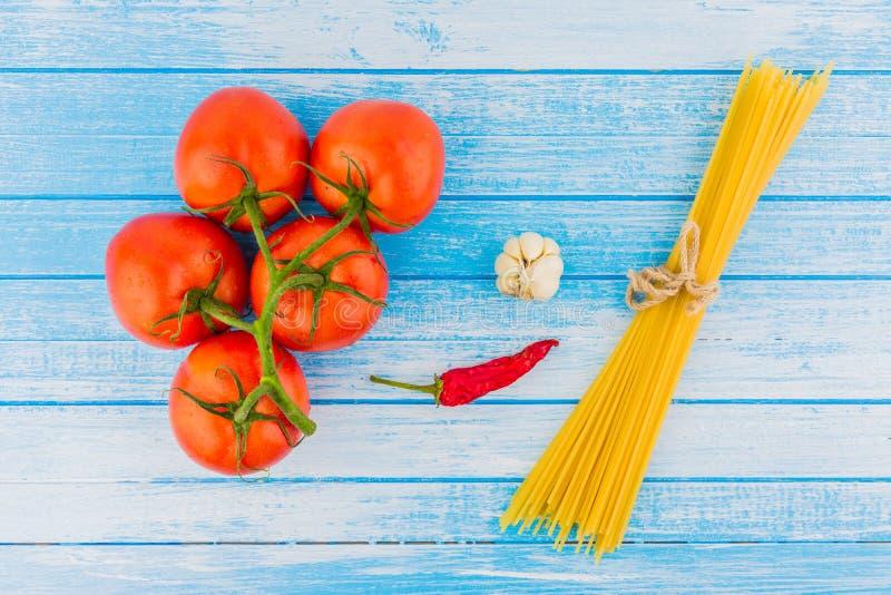 Nya organiska tomater med peppar och Unc för Waterdrops vitlök röd arkivfoton