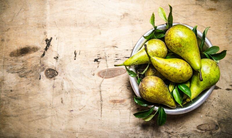 Nya päron i bunke med sidor på trätabellen royaltyfri fotografi
