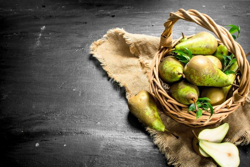 Nya päron i en gammal korg royaltyfri fotografi