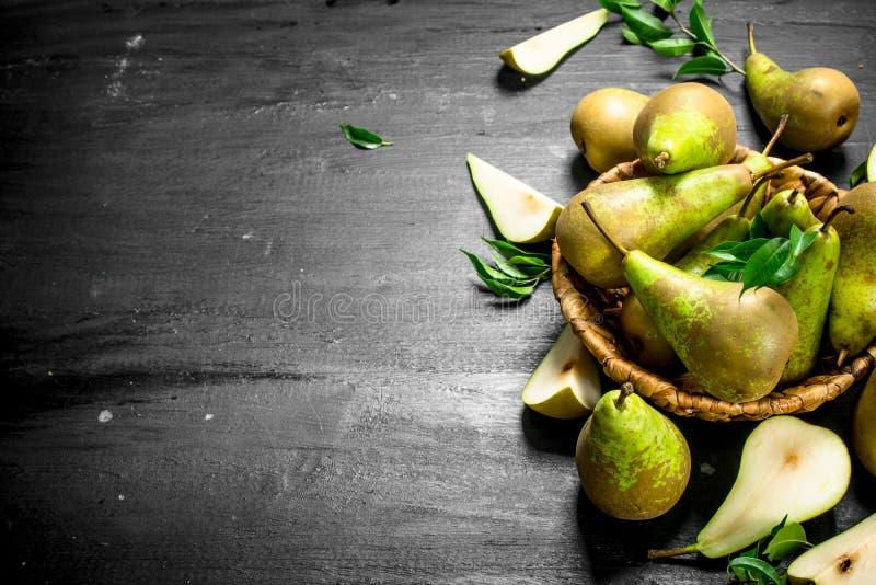 Nya päron i en gammal korg royaltyfria foton