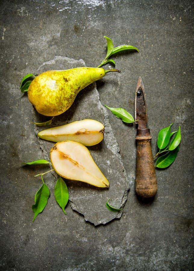 Nya päron på en sten står med sidor arkivfoton