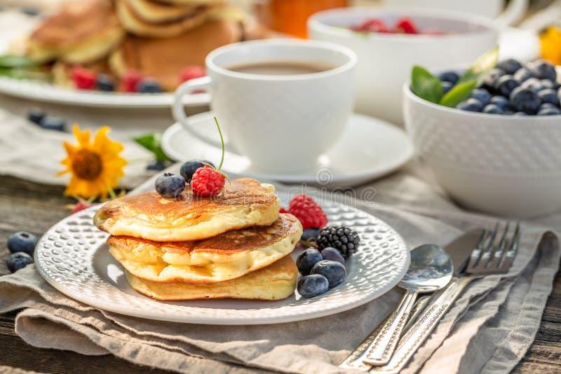 Nya pannkakor med hallon, blåbär och honung royaltyfria bilder