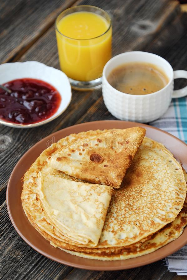 Nya pannkakor med jordgubbedriftstopp, kaffe och fruktsaft arkivbilder