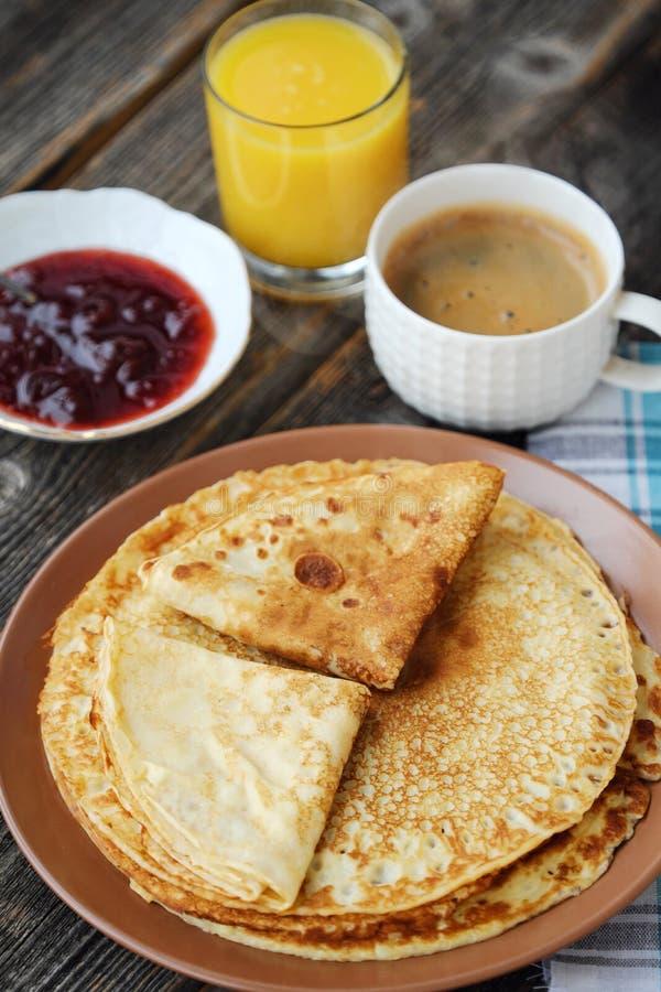 Nya pannkakor med jordgubbedriftstopp, kaffe och fruktsaft arkivfoto