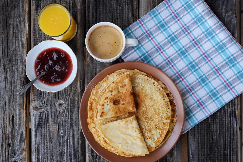 Nya pannkakor med jordgubbedriftstopp, kaffe och fruktsaft arkivfoton