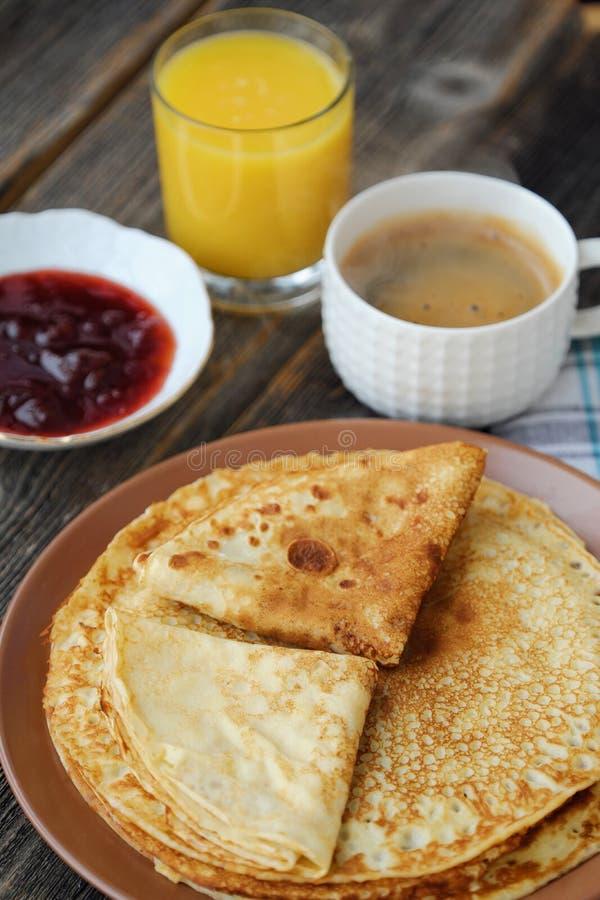 Nya pannkakor med jordgubbedriftstopp, kaffe och fruktsaft royaltyfria bilder