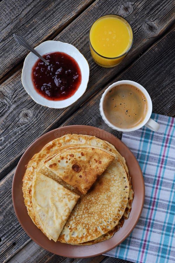 Nya pannkakor med jordgubbedriftstopp, kaffe och fruktsaft royaltyfri foto