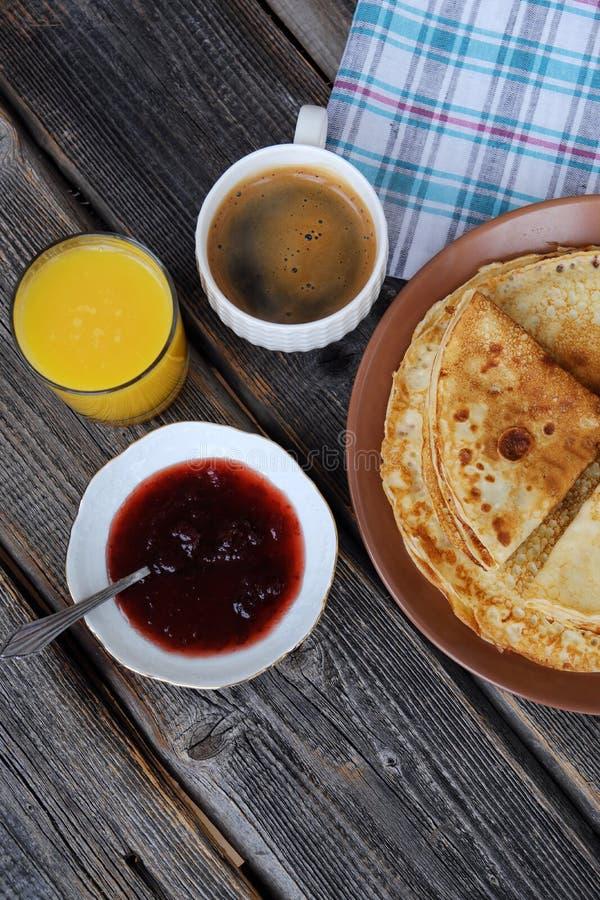 Nya pannkakor med jordgubbedriftstopp, kaffe och fruktsaft royaltyfria foton