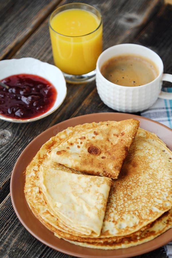 Nya pannkakor med jordgubbedriftstopp, kaffe och fruktsaft royaltyfri bild