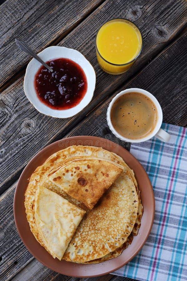 Nya pannkakor med jordgubbedriftstopp, kaffe och fruktsaft royaltyfri fotografi