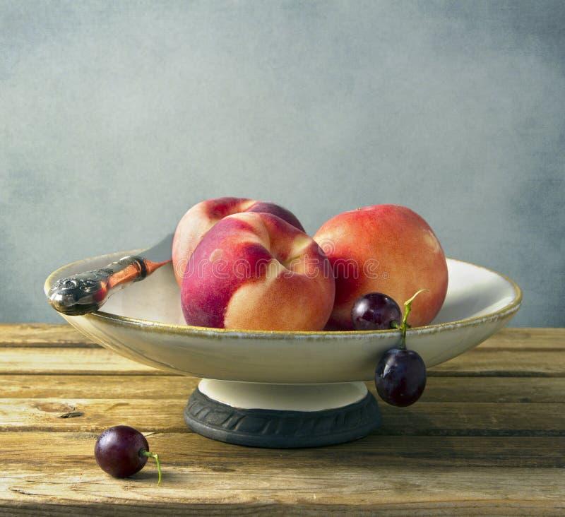 Nya persikor i tappningplatta fotografering för bildbyråer