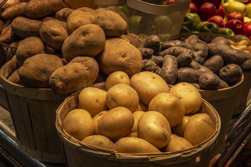 Nya potatisar i en trähink på marknaden royaltyfria bilder
