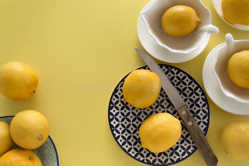 Nya rå citroner och porslinbordsserviser på ny gul bakgrund Stilleben bakgrund arkivfoto