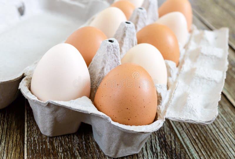 Nya rå fega ägg i lådaäggask på träbakgrund arkivfoton