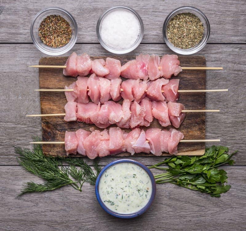 Nya rå fega stycken på kryddade steknålar saltar, och vitlöksås gör grön på en skärbräda royaltyfri foto
