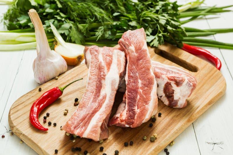 Nya rå grisköttstöd med lager av fett med grönsaker och peppar på en skärbräda royaltyfri foto