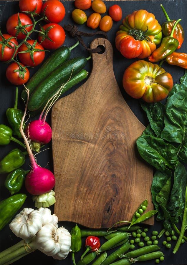 Nya rå ingredienser för sund matlagning- eller salladdanande med mörk träbitande baoard i mitten, bästa sikt, kopia arkivbilder