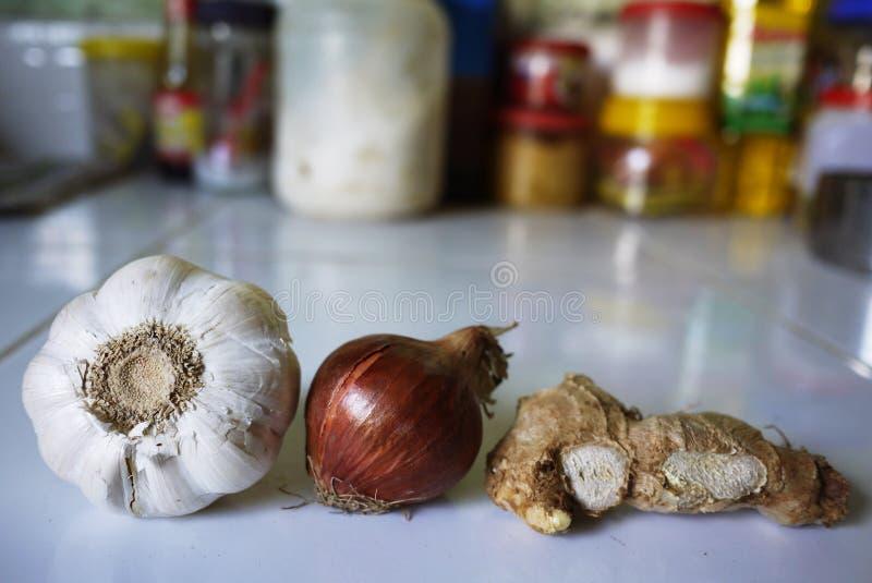 Nya rå ingredienser, vitlök, röd lök och ingefära i kök arkivfoto