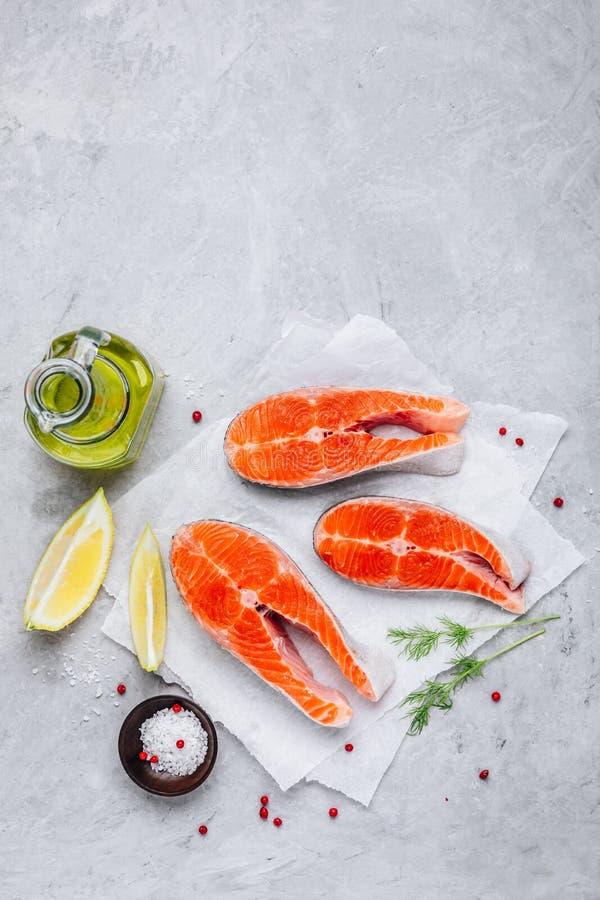 Nya rå laxbiffar med citronen och dill för att laga mat på grå bakgrund fotografering för bildbyråer