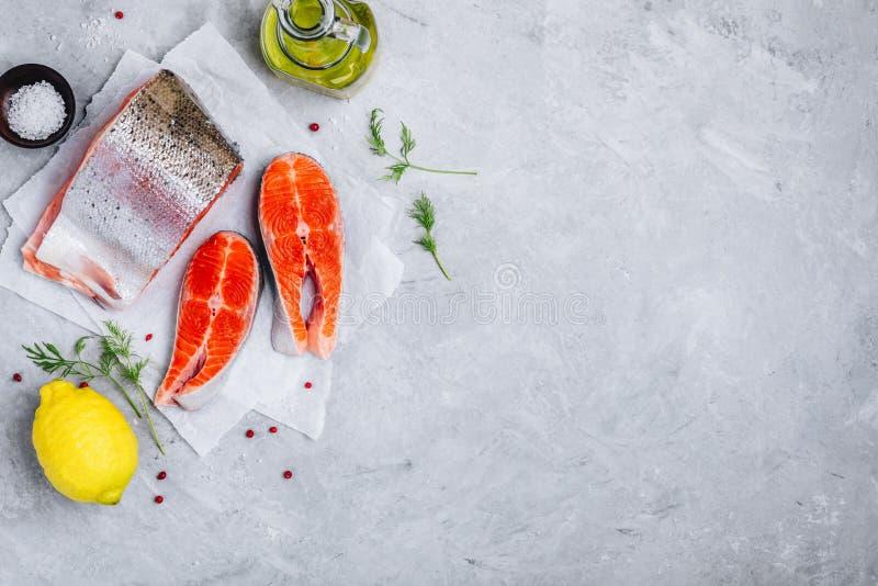 Nya rå laxbiffar med citronen och dill för att laga mat på grå bakgrund royaltyfri foto