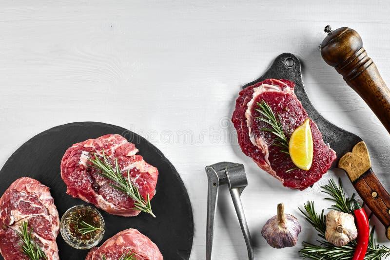 Nya rå nötköttbiffar med örter, vitlök, olivolja, peppar, saltar och rosmarin på svart bräde: Fläskkarré Striploin arkivfoto