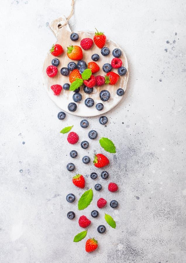 Nya rå organiska bär på rund tappning stiger ombord bakgrund Top beskådar Jordgubben, hallonet, blåbäret och mintkaramellen spric fotografering för bildbyråer