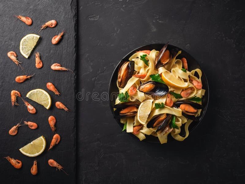 Nya rå räkor eller kokade röda räkor med kryddor, och citronen kritiserar på stenen på mörker stenar bakgrund Den havs- bästa sik arkivfoto