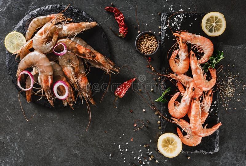 Nya rå räkor och kokade röda räkor med kryddor kritiserar på stenen på mörker stenar bakgrund Den havs- bästa sikten, lägger fram arkivfoton
