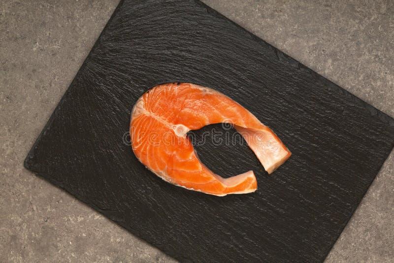 Nya rå Salmon Red Fish Steak på en svart kritiserar plattan royaltyfri bild