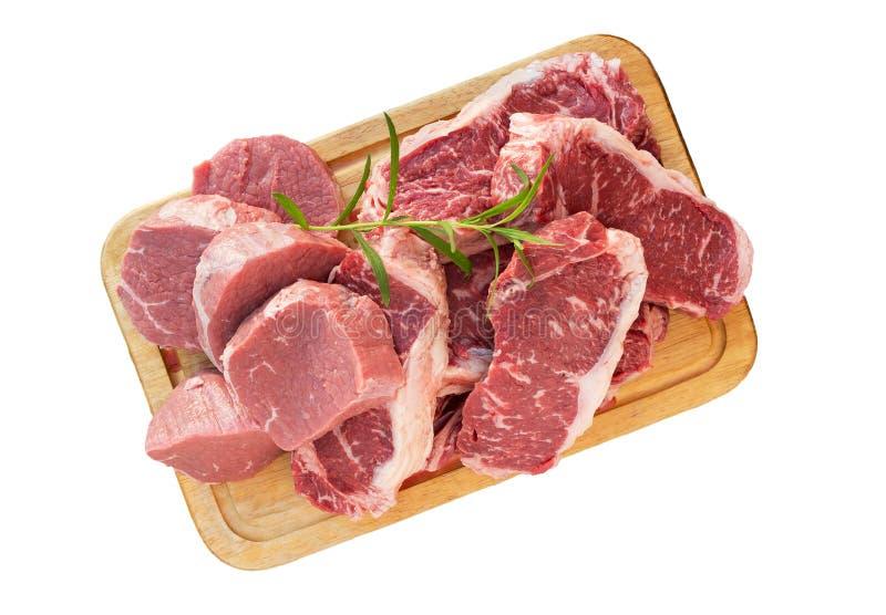 Nya rå skivor för nötköttköttbiff på träsnittbrädet som isoleras på royaltyfria foton