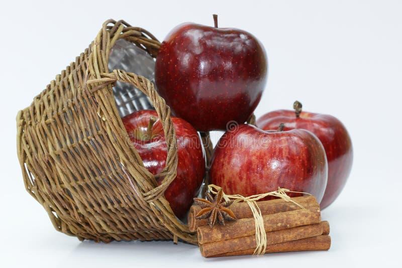 Nya röda äpplen i korgen, kanel på vit bakgrund royaltyfri foto