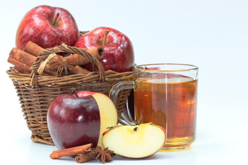Nya röda äpplen i korgen, kanel på vit bakgrund arkivbild