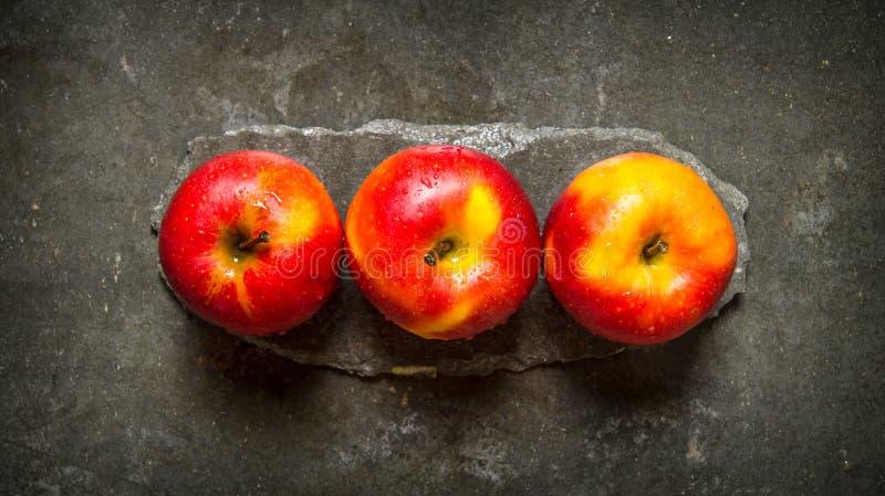 Nya röda äpplen på en stenställning royaltyfri fotografi